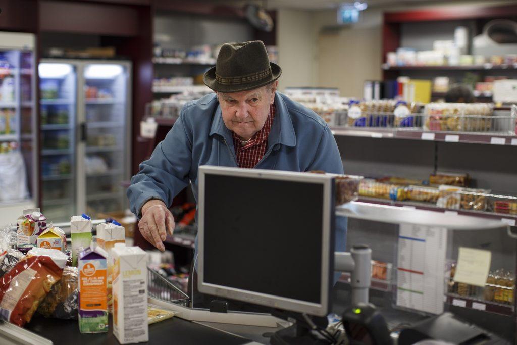 El señor Van E. haciendo la compra en la tienda de alimentación, situada en la galería central, donde también se encuentran el restaurante y la sala para los clubes de actividades. © Hogeweyk