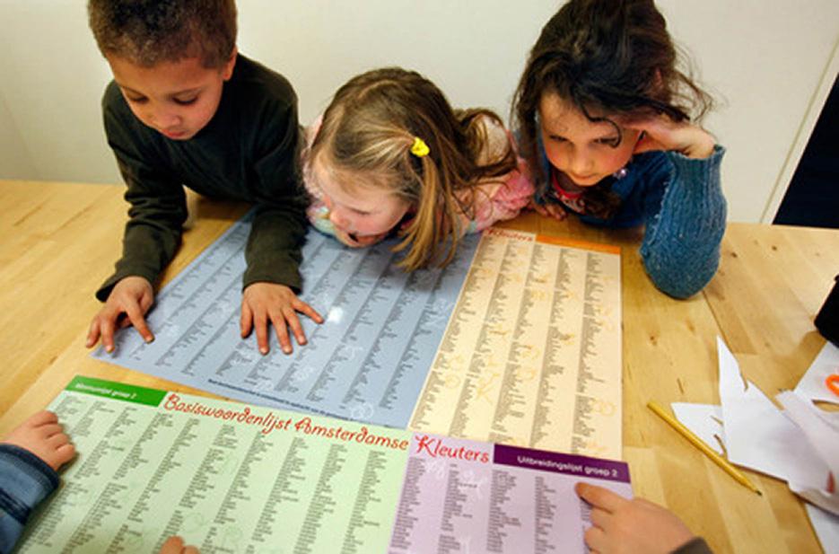 Niños de primaria de una escuela de Ámsterdam, con un listado de vocabulario en neerlandés. A la derecha, profesora de primer grado del método Montessori. Foto: Elckerlyc School Leiderdorp